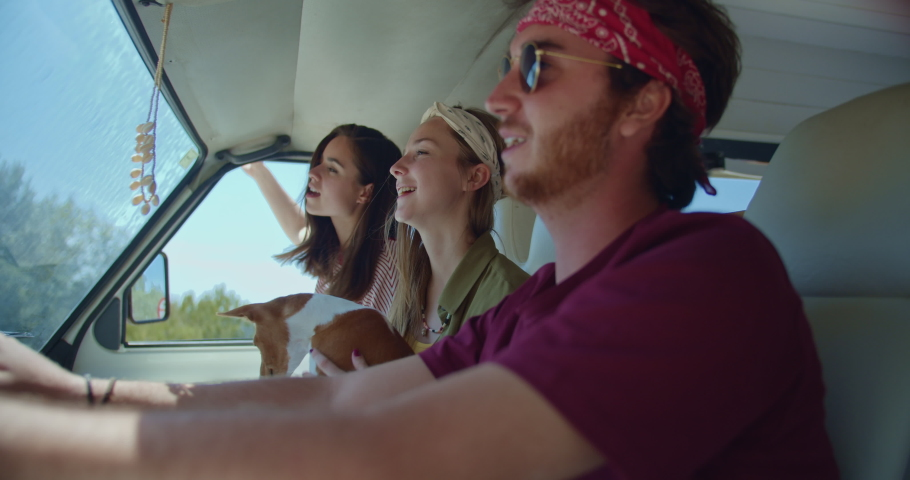 Cheerful friends dancing in camper van enjoying road trip in Europe with puppy dog, Living in Camper Van Travel Adventures Explore, happy friends having fun traveling trough Europe on vintage van | Shutterstock HD Video #1036901630