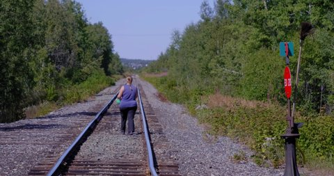 Amos, Québec/Canada 08-24-2019: A woman walking  on the railway in a forest in Abitibi.