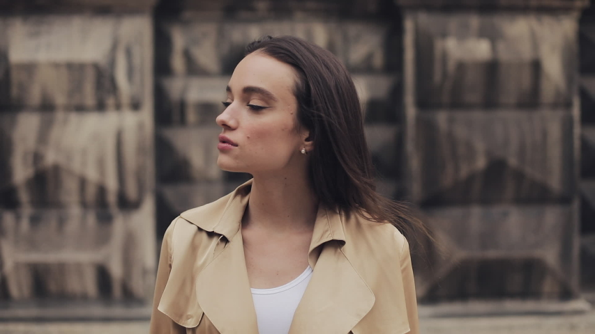 Portrait of Pretty Young Girl Wearing Earings and Beige Trench Standing Turning her Head and Smiling Close Up | Shutterstock HD Video #1036909220
