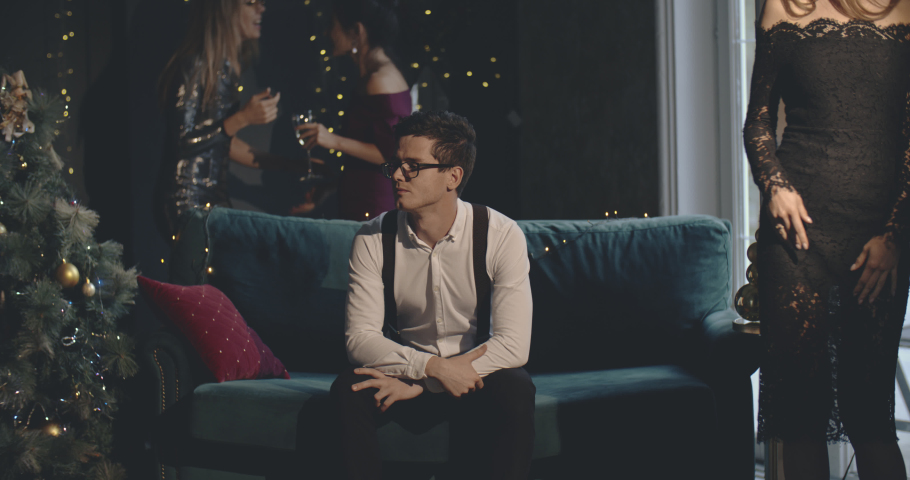Unhappy man feeling alone at xmas noisy party. Loneliness, christmass, new year concept. Medium shot on 4k RED camera with 12 bit color depth.   Shutterstock HD Video #1036916870