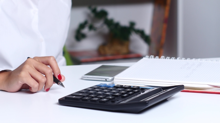 Woman doing calculations in the office and writes | Shutterstock HD Video #1036983470