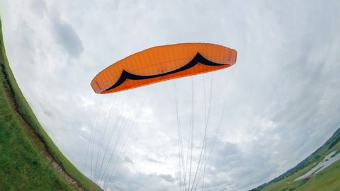 Athlete controls a paraglider while flying over field.