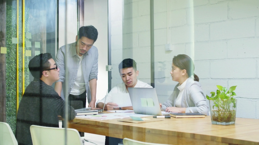 Group of young asian entrepreneurs meeting in office discussing business plan | Shutterstock HD Video #1037075420