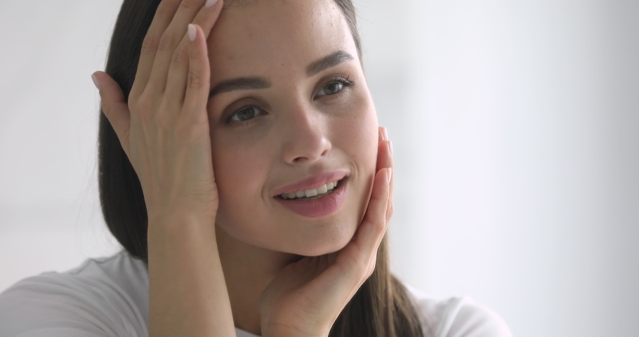 Happy attractive young woman touching pretty face after applying cream do make up looking in mirror enjoy natural beauty and healthy clean soft moisturized hydrated skin care treatment, close up view | Shutterstock HD Video #1037145020