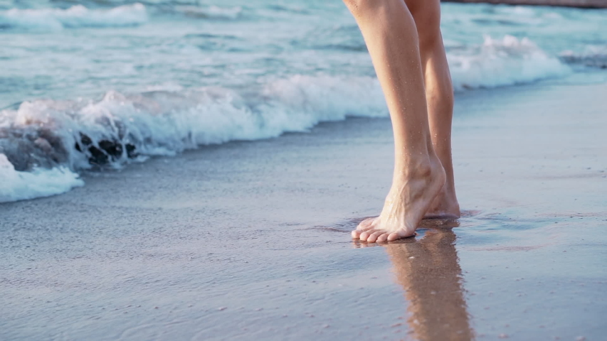 Legs of a young slender ballet dancer girl standing on sandy sea shore. Feet washed by warm waves with foam | Shutterstock HD Video #1037145560