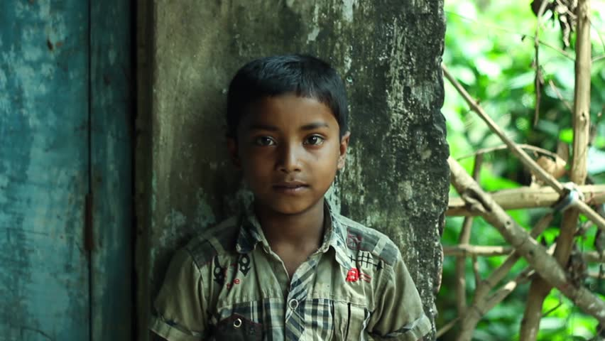 Portrait of a village boy in India. He stands by a worn wall and looks thoughtfully at the camera.