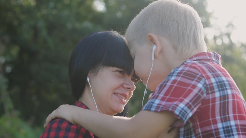 Happy family funny nature slow motion video teamwork outdoors. Mom and son listen to lifestyle music on smartphone in the same headphones for two . happy family mother woman and son little boy spend   Shutterstock HD Video #1037217920