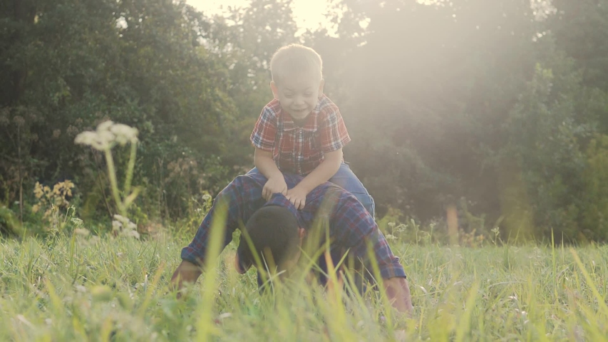Dad and son lifestyle happy family play push ups slow motion funny video . father man and son little a boy push ups in nature laugh and play   Shutterstock HD Video #1037217980