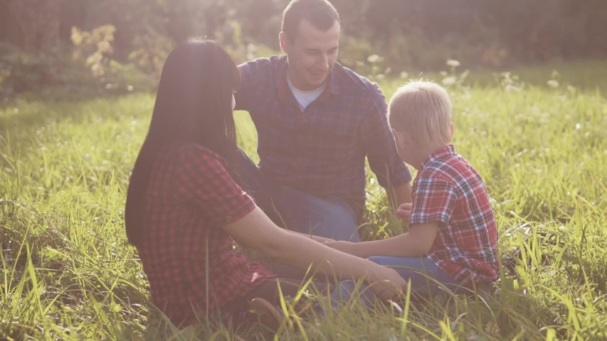 Happy family teamwork outdoors concept outdoors slow motion video. mom dad and son in nature are sitting on the grass have fun playing. mom girl dad man and son boy happy family lifestyle   Shutterstock HD Video #1037218010
