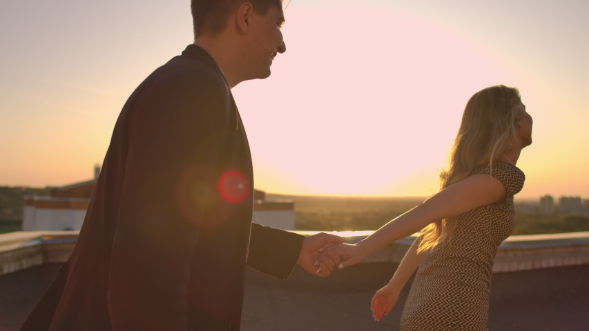 Young couple holding hands walking woman leading boyfriend the roof of the building at sunset POV travel concept. Carefree free lovers run on the roof laughing and smiling.   Shutterstock HD Video #1037258240