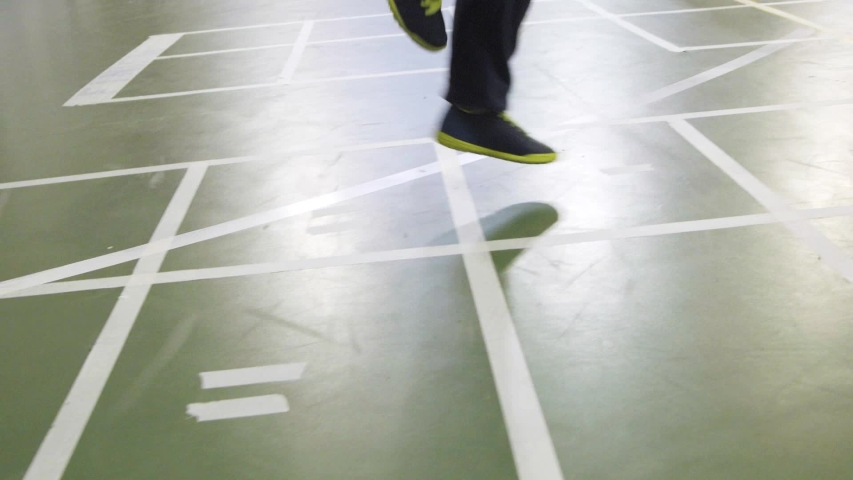 Elementary school gym class. Kids jumping on one foot on the floor squares | Shutterstock HD Video #1037264900
