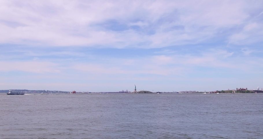 Distant view of the Statue of Liberty from the Battery Park in Lower Manhattan, New York. | Shutterstock HD Video #1037285300