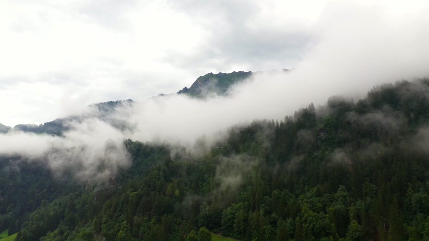 Aerial, tracking, drone shot, overlooking foggy forest, in the swiss alps, near the Lauterbrunnen village, on a cloudy, summer day, in Bernese Oberland, Switzerland | Shutterstock HD Video #1037307290