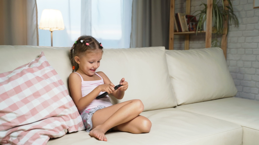 Little Girl Child Home On Sofa Playing On Smartphone   Shutterstock HD Video #1037314490