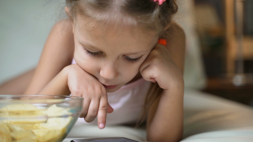 Little Girl Child Home On Sofa Playing On Smartphone   Shutterstock HD Video #1037314550