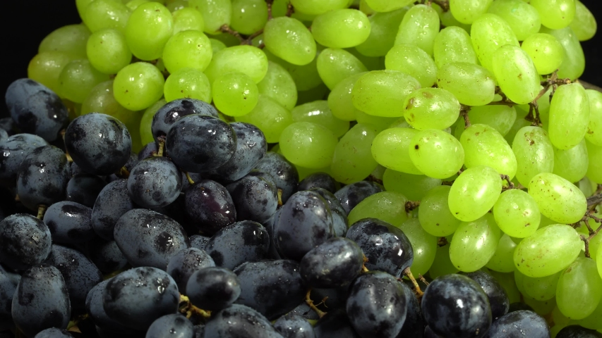 Black and green grapes rotation background. Grape close up