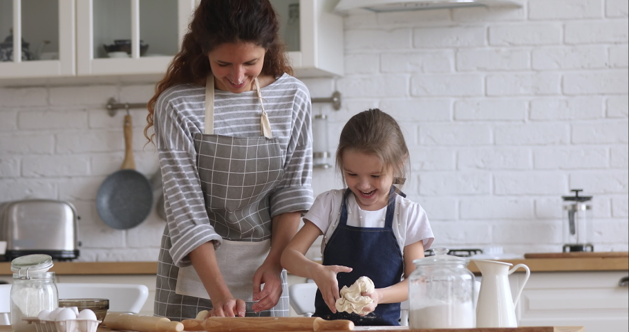 Loving happy mom teaching cute kid daughter learning kneading dough with rolling pin, funny child girl helping mother preparing cookies cooking baking pastry playing in modern kitchen at home | Shutterstock HD Video #1037333450