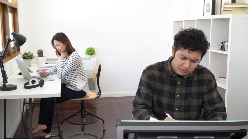 4K Wide shot of young adult smart asian creatives man and woman working in modern small start up business office with drawing desk, laptop computer and digital tablet with wireless technology.  | Shutterstock HD Video #1037346710