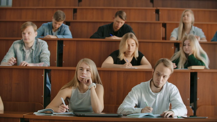 In the Classroom Multi Ethnic Students Listening to a Lecturer and Writing in Notebooks. Smart Young People Study at the College | Shutterstock HD Video #1037361230