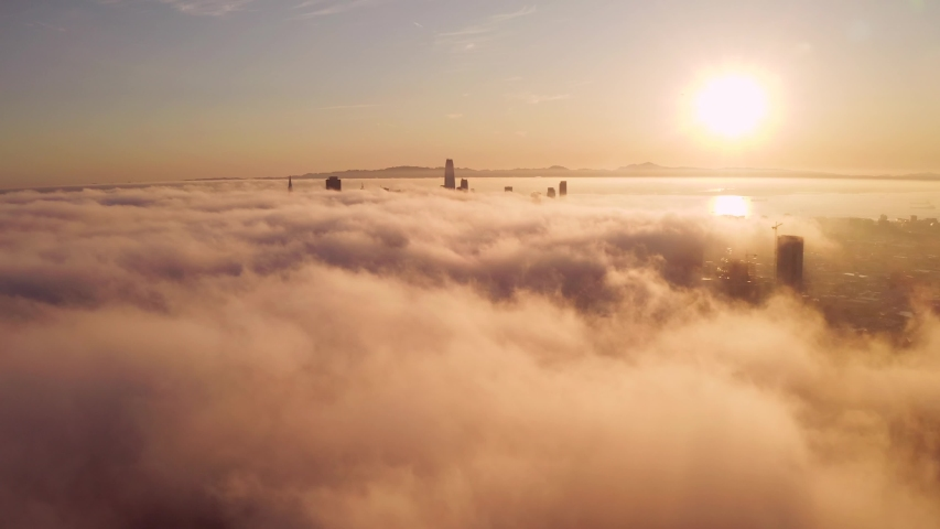 Flying over the clouds during morning sunrise in San Francisco with skyscrapers rising above the clouds. Beautiful Californian morning in San Francisco. | Shutterstock HD Video #1037374190