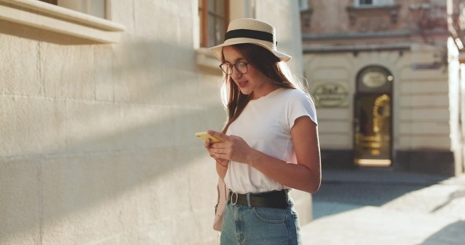 Pretty Young Woman Walking in the City. Using her Mobile Phone. Chatting on it. Typing a Message. Girl Looking Excited, Satisfied. Smiling Happily | Shutterstock HD Video #1037471150