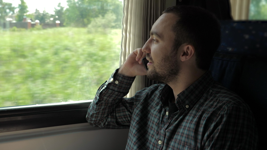 Handsome man talking on mobile phone in train. | Shutterstock HD Video #1037487830