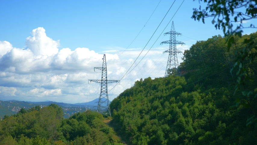 Power lines among mountains and trees against the sky. copy space | Shutterstock HD Video #1037758370