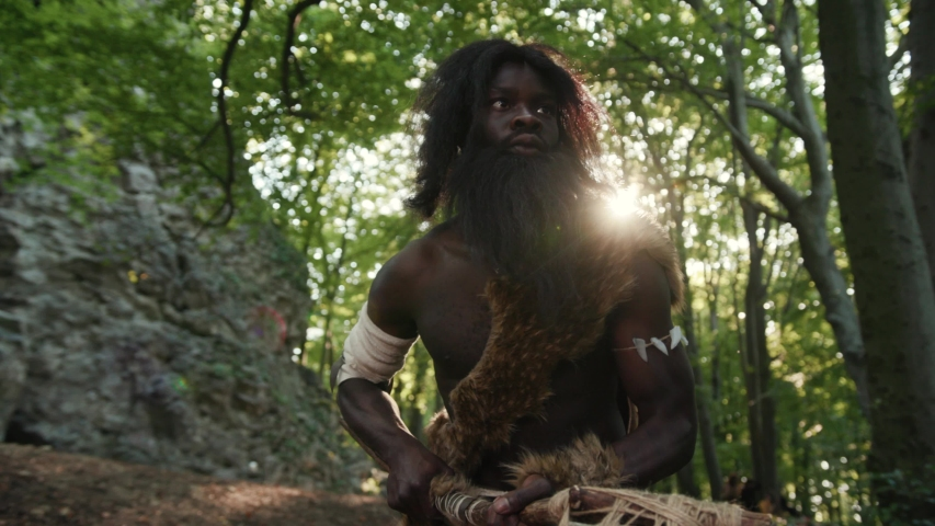 Savage caveman in mammoth fur hunting animals in forest jungle. African aborigine of nomadic neanderthal tribe. Wildlife and people. | Shutterstock HD Video #1037834270