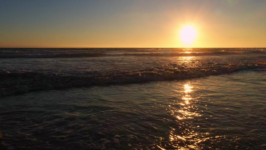 Flying backwards under pier during sunset on the ocean at Newport Beach California. | Shutterstock HD Video #1037861030