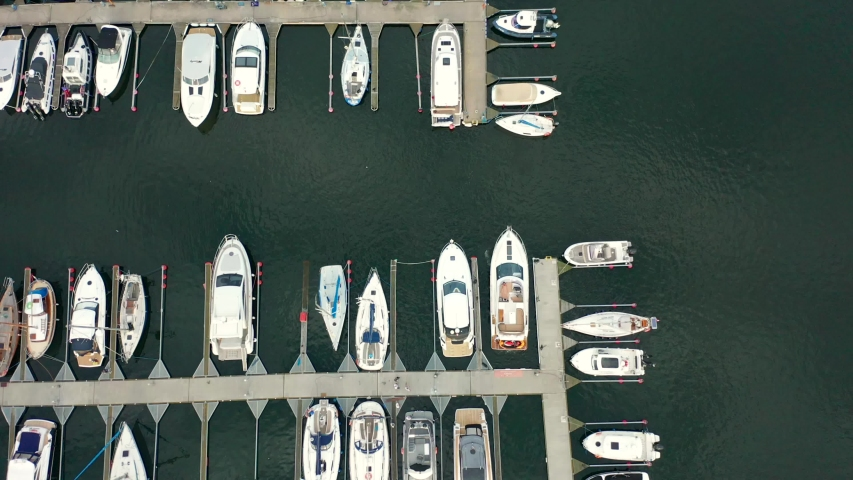 Aerial view of a white motor yacht. Yacht enters the bay in the parking lot. Gdynia, Poland. Many different yachts, catamarans moored to piers. Drone shot 4K.   Shutterstock HD Video #1037870150