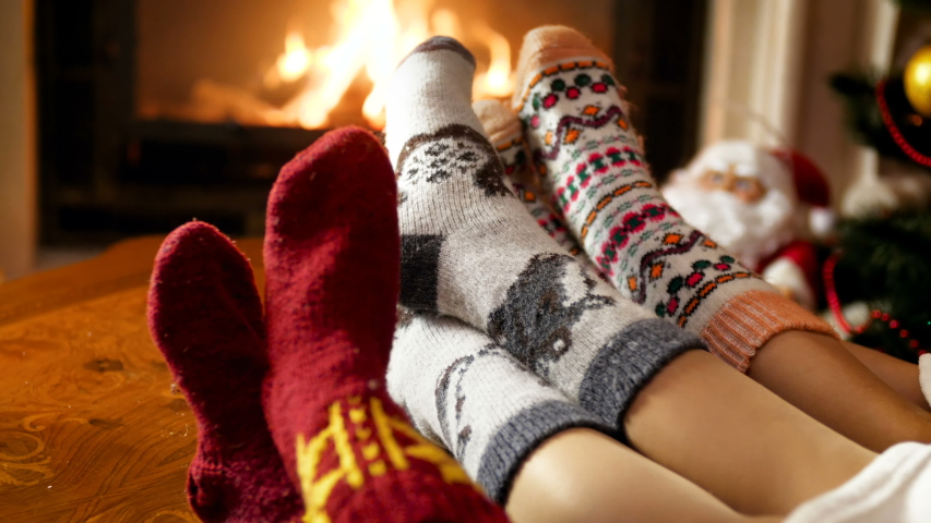 Closeup 4k video of three pairs of feet wearing warm woolen socks warming in living room by the burning fireplace. People relaxing on winter holidays and celebrations at home | Shutterstock HD Video #1037870870