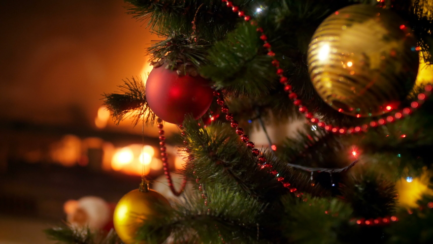Closeup 4k video of glowing and glittering colorful lights on LED garland covering Christmas tree against burning fireplace. Perfect shot for winter celebrations and holidays | Shutterstock HD Video #1037879060