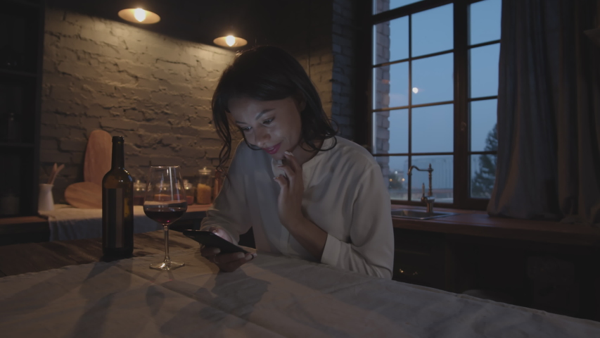 Panning of mixed-race woman sitting at kitchen table at night time, drinking red wine and using her telephone | Shutterstock HD Video #1037965010