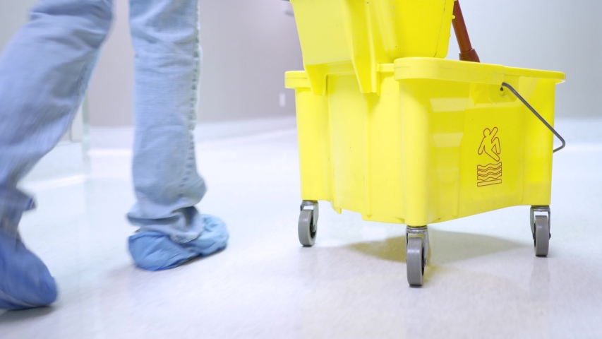 Janitor walking with yellow mop bucket down medical hallway with booties for sanitation on shoes at hospital