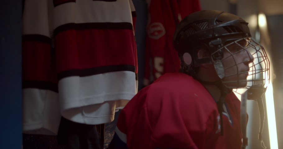 Hockey player puts on helmet in change room and gets up ready to get on the ice and win the playoffs | Shutterstock HD Video #1038217850