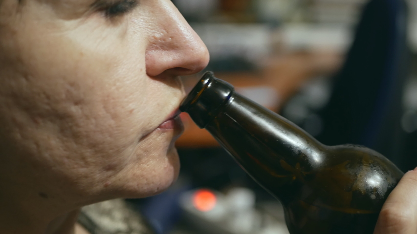 Caucasian woman drinks beer from a bottle in the office. close-up | Shutterstock HD Video #1038469100
