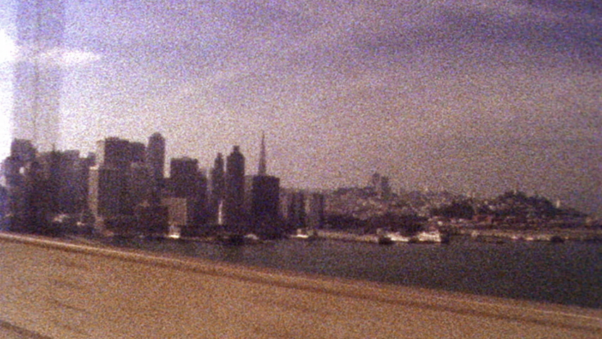 Old looking archival footage of San Francisco skyline while driving across Golden Gate Bridge