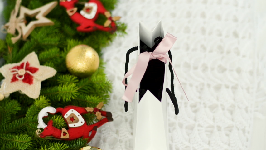 Hands of a young girl untie the ribbons on a white gift bag. The main background is knitted knitwear. Against the background, the Christmas composition is decorated with decorative toys: two Christmas | Shutterstock HD Video #1038583310