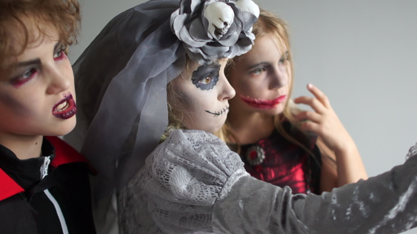 Three teenagers in halloween makeup and costumes take selfies. Close up. Halloween celebration, halloween traditions   Shutterstock HD Video #1038716900