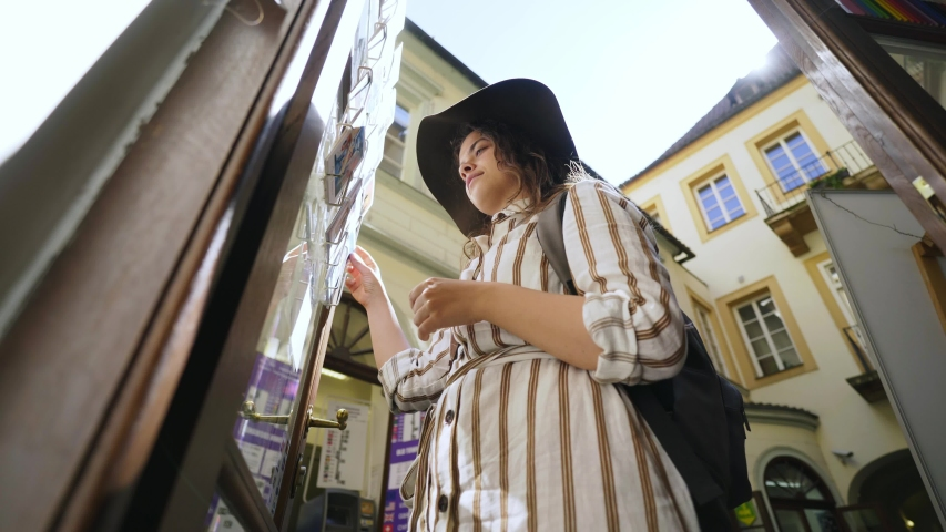 Young woman looking post cards in souvenir shop at old city centre of Prague. From below view elegant lady in hat choosing greeting cards while standing on street in backlit  | Shutterstock HD Video #1038742490
