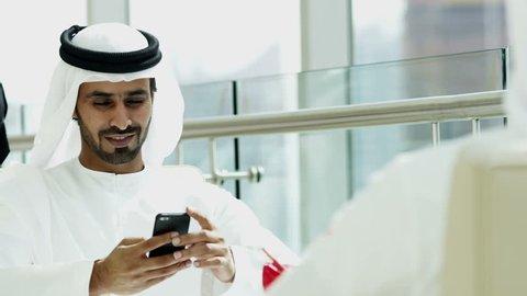 Arab male kandura touch screen smart phone social leisure hotel travel lifestyle