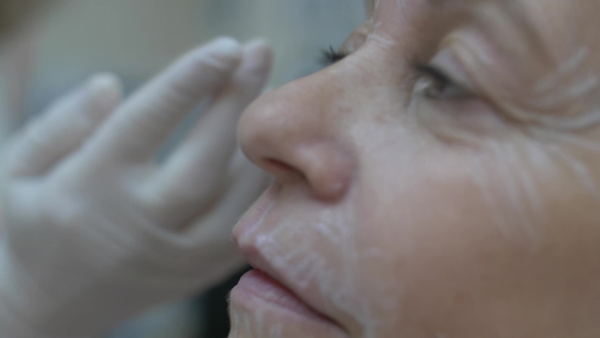 Cosmetic clinic, woman getting a Hyaluronic acid injection it is used to reduce the appearance of fine lines and wrinkles, facial folds, and to create structure, framework and volume of the lips | Shutterstock HD Video #1038761690