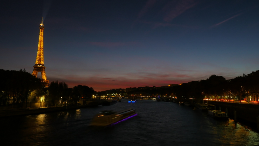 In Paris, the Eiffel Tower lights up and boats traverse the Seine River in time lapse at sundown. | Shutterstock HD Video #1038816440