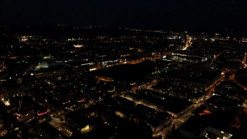Aerial shot, drone flying forwards over large buildings at night. Illuminated by street lights and building. Helsinki City | Shutterstock HD Video #1038835700