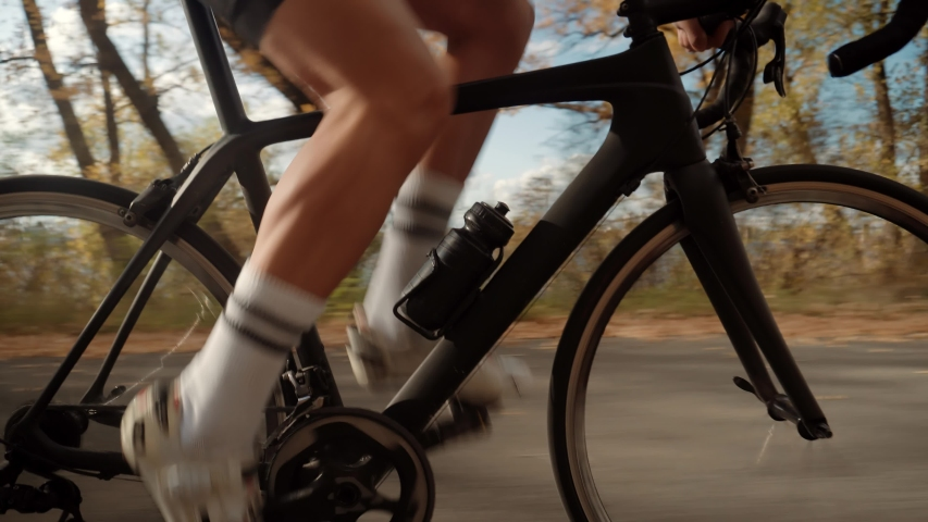 Cyclist Twists Pedals And Riding On Road Bicycle.Cycling Athlete At Sunset On City Park.Gear System Road Bicycle And Bike Wheel Rotation.Close-Up Cyclist Pedaling On City Park At Sunset.Sport Concept | Shutterstock HD Video #1038905480