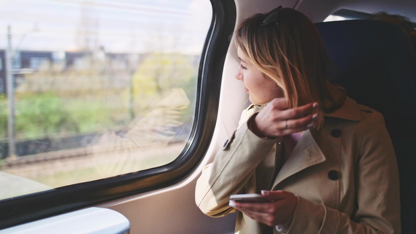 Young Woman Using Smartphone on a Train. SLOW MOTION. Business woman Looking Out of a Train Window during her daily commute, using cell phone. Social network, planning, communicating.   Shutterstock HD Video #1038908480