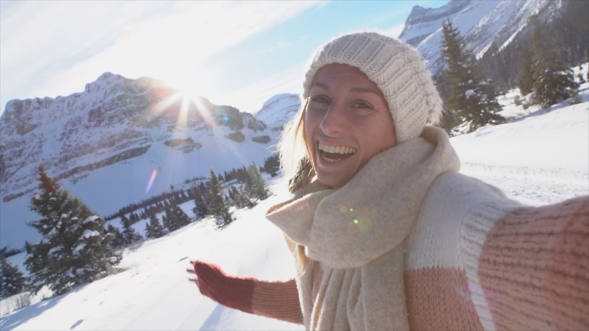 Young woman on a winter vacation takes a selfie surrounded by snowy landscape. Woman travelling in Canada during Christmas season takes a video selfie. Slow motion  | Shutterstock HD Video #1038969410