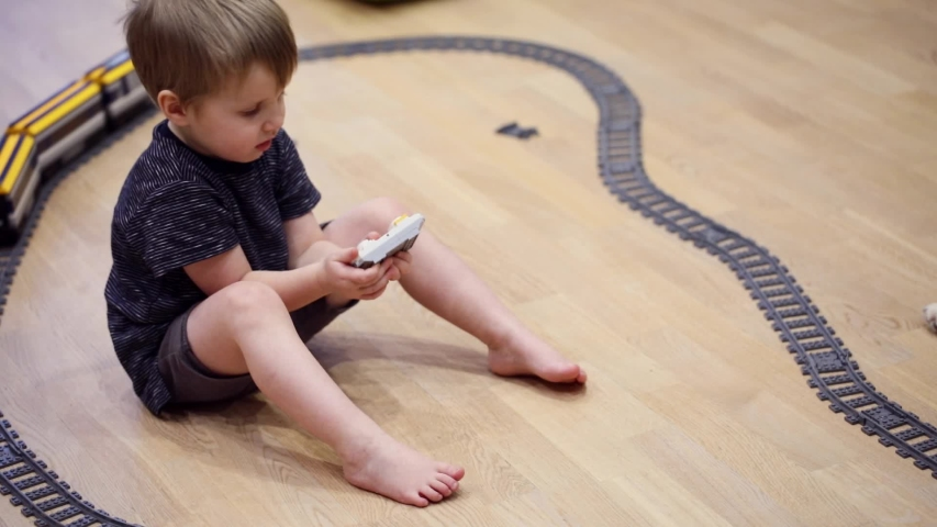 Four years old child boy play with radio train, constructed toy railroad at home. Toddler boy playing. Educational toys for preschool child, indoor playground, lifestyle concept   Shutterstock HD Video #1039012040