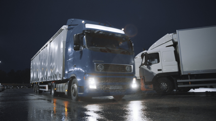 Blue Semi-Truck with Cargo Trailer Drives Off From Overnight Parking Space where Other Trucks are Standing. Long Haul Truck Leaves Parking Lot, Transporting Cargo / Goods Across Continent. Rainy Night | Shutterstock HD Video #1039037180