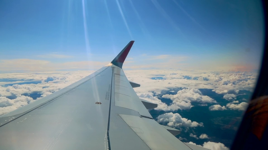 Beautiful cloud and wing of airplane from window with a nice blue sky #1039047620